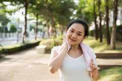 Female runner wipe sweat after running. Portrait of attractive beautiful smile young Asian woman runner use pink towel to wipe sweat at outdoor park for sport stock photos
