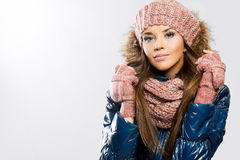 Portrait of attractive beautiful young woman wearing gloves, scarf and winter cap, white background.  stock photo