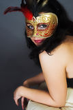 Portrait of attractive beautiful young woman wearing gold carnival mask royalty free stock photography