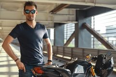Portrait of attractive biker standing next to motorcycle at parking. Urban background. Portrait of attractive biker wearing sunglasses and standing next to stock photo