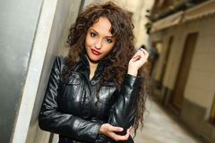 Attractive black woman in urban background wearing leather jacke. Portrait of attractive black woman in urban background wearing leather jacket Royalty Free Stock Photo