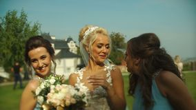 Portrait of the attractive blond bride and her pretty bridesmaids smiling and posing at camera in the blooming garden. stock video