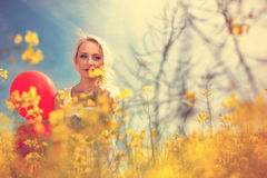Portrait of attractive blond female in yellow floral field Stock Photo