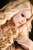 Portrait of an attractive blond woman with long curly hair, isolated on black studio shot Royalty Free Stock Photos