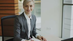 Portrait of Attractive blonde businesswoman sitting at table writing in notebook smiling into camera in modern office. Indoors stock video footage