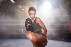 Beautiful girl in boxing gloves ready to kick Royalty Free Stock Images