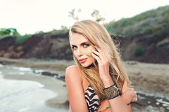 Portrait of attractive blonde girl with long hair posing on rocky beach. She wears bikini and ornamentation. She is. Portrait of attractive blonde girl with long royalty free stock image