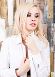Portrait of attractive blonde girl standing on wood wall background. She has blue eyes and dressed in a man`s shirt.  Royalty Free Stock Photography