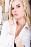 Portrait of attractive blonde girl standing on wood wall background. She has blue eyes and dressed in a man`s shirt Stock Photos