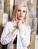 Portrait of attractive blonde girl standing on wood wall background. She has blue eyes and dressed in a man`s shirt Stock Photo