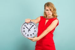 Attractive woman with clocks. Portrait of attractive blonde woman in red isolated on blue background holding clocks time limit punctuality concept Royalty Free Stock Image