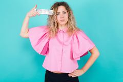 Attractive woman with remote control. Portrait of attractive bored curly-haired woman in pink blouse isolated on blue backgroung holding remote control near her Royalty Free Stock Images