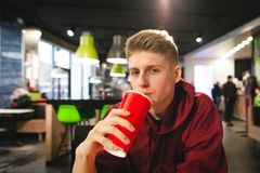 Portrait of attractive boy with a large red glass in his hand, drinking a stake and looking at the camera stock image