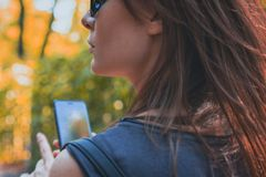 Portrait attractive of a brown-haired woman with a phone in her hand for a walk. Toned royalty free stock photography