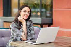 Portrait of attractive brunette female with coverlet, spends free time in outdoor cafeteria, develops new project, uses laptop com. Puter, high speed internet Stock Image
