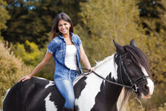 Portrait of attractive brunette female ride. R sitting on her horse and smiling Stock Photo