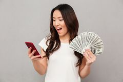 Portrait of attractive brunette female 20s winning lots of money. Dollar currency using her smartphone isolated over gray background Stock Photos