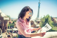 Portrait of attractive brunette girl looking at map while travelling Royalty Free Stock Images