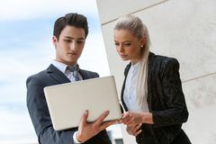 Young business partners reviewing data on laptop. Stock Photos