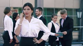 Portrait of attractive business lady making an important phone call and her colleagues standing behind and chatting stock video footage