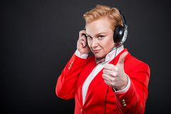 Portrait of attractive business woman holding headphones showing Stock Images