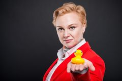 Portrait of attractive business woman holding rubber duck. On black background with copyspace advertising area royalty free stock image
