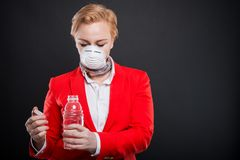 Portrait of attractive business woman holding water wearing mask Stock Photo
