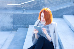 Portrait of attractive business woman reading a tablet and sitting outdoors Royalty Free Stock Photo