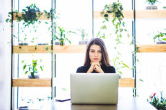 Portrait of attractive business woman sitting in chait and working at laptop online. Royalty Free Stock Photos