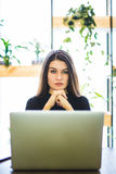Portrait of attractive business woman sitting in chait and working at laptop online. Royalty Free Stock Photo