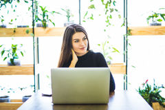 Portrait of attractive business woman sitting in chait and working at laptop online. Stock Image