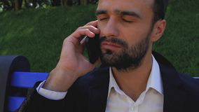 Portrait of an attractive businessman with a beard waiting for a phone call while sitting on a park bench. bearded man in a stock video