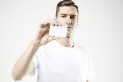 Portrait of attractive businessman holding blank business card, empty space for layout, with white background Royalty Free Stock Image