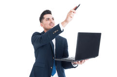 Portrait of attractive businessman holding laptop and pointing u Stock Photo