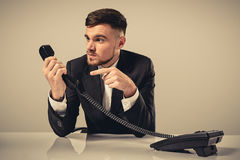 Portrait of attractive businessman holding telephone in his hand Stock Images