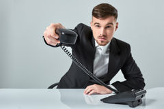 Portrait of attractive businessman holding telephone in his hand. This call is for you concept Royalty Free Stock Images