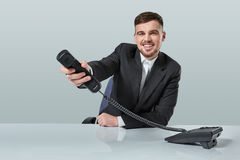 Portrait of attractive businessman holding telephone in his hand. This call is for you concept Royalty Free Stock Photo