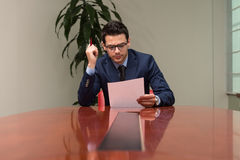 Portrait Of Attractive Businessman Reading Paper In Office Stock Photography