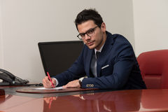 Portrait Of Attractive Businessman Reading Paper In Office Stock Photo