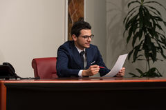 Portrait Of Attractive Businessman Reading Paper In Office Stock Image