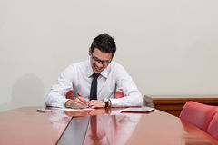 Portrait Of Attractive Businessman Reading Paper In Office Stock Images