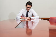 Portrait Of Attractive Businessman Reading Paper In Office Royalty Free Stock Photos