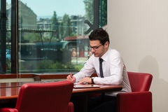 Portrait Of Attractive Businessman Reading Paper In Office Royalty Free Stock Photo