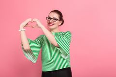 Businesswoman with hair bun. Portrait of attractive businesswoman with hair bun in striped blouse and eyeglasses showing heart sign gesture isolated on pink stock photos