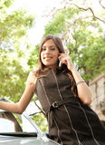Businesswoman leaning on car with phone. Royalty Free Stock Photo