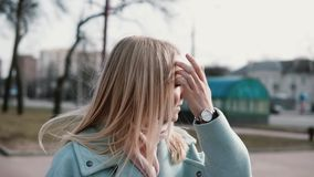 Portrait of attractive Caucasian blonde woman. Anticipation and excitement. Adult 30s female in stylish coat and scarf. stock footage