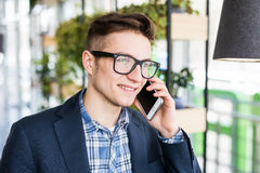 Portrait of attractive caucasian man in casual shirt and glasses talking on cellular phone at workplace. Royalty Free Stock Photography