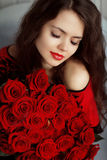 Portrait of attractive Caucasian smiling woman with red roses bo Royalty Free Stock Photography