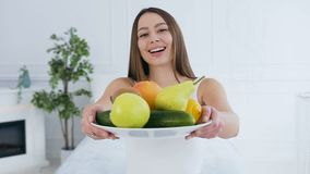Portrait of attractive caucasian woman stretching out plate with fruits to the camera. stock video