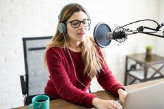 Female live on online radio. Portrait of attractive caucasian woman wearing headphones and talking at online radio station royalty free stock image